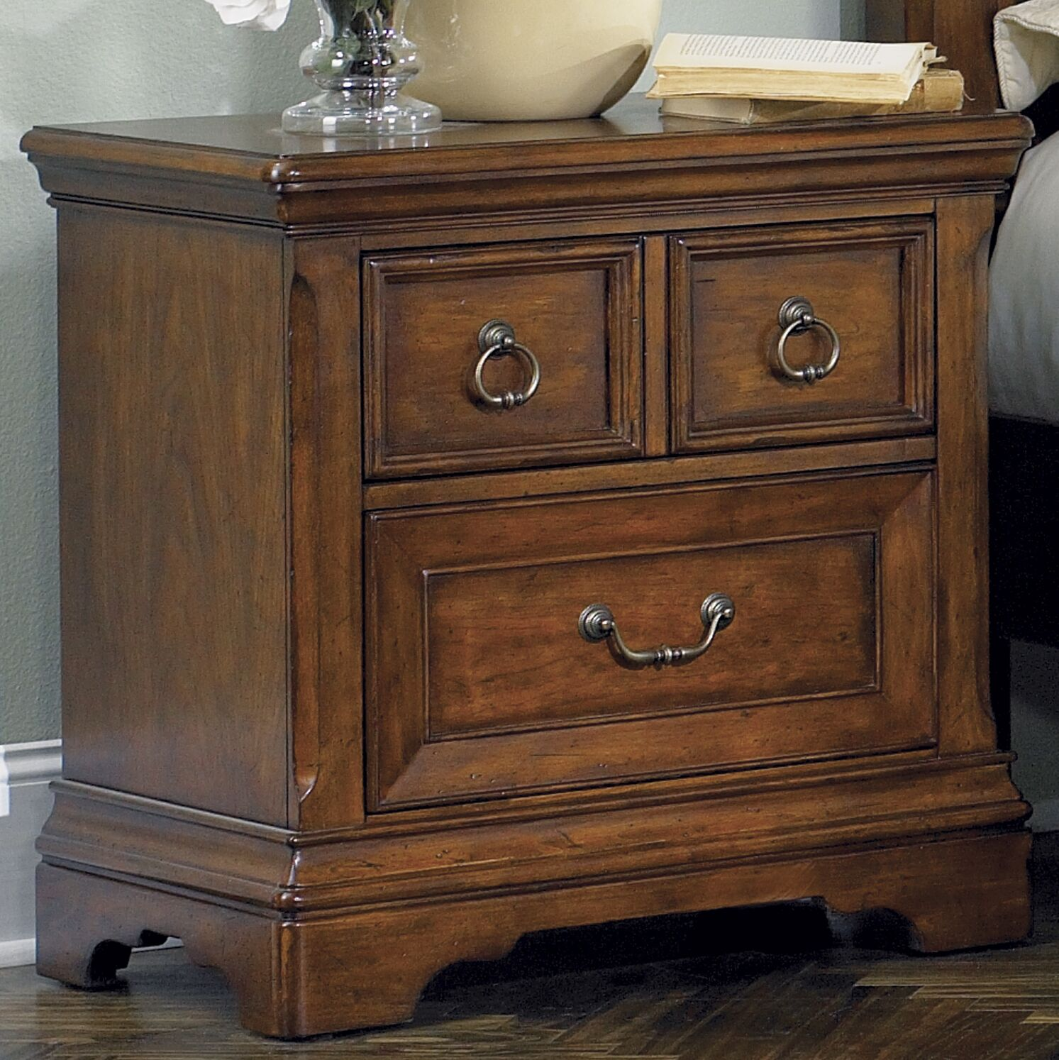 Features: -Dust proofing on bottom case.-Antique brass bail pull and ring hardware.-Full extension metal side drawer glides.-Beaded molding.-Bracket feet.-French and English dovetail construction.-Chestnut finish.-Scrolled metal accents.-Laurelwood co...